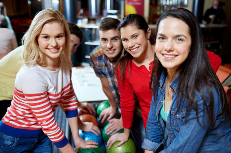 38817434 - people, leisure, sport, friendship and entertainment concept - happy friends in bowling club